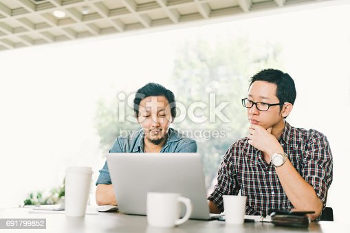 istock Handsome Asian business colleagues or college students work together using laptop, startup project meeting or teamwork brainstorm concept, at coffee shop or modern office 691799852