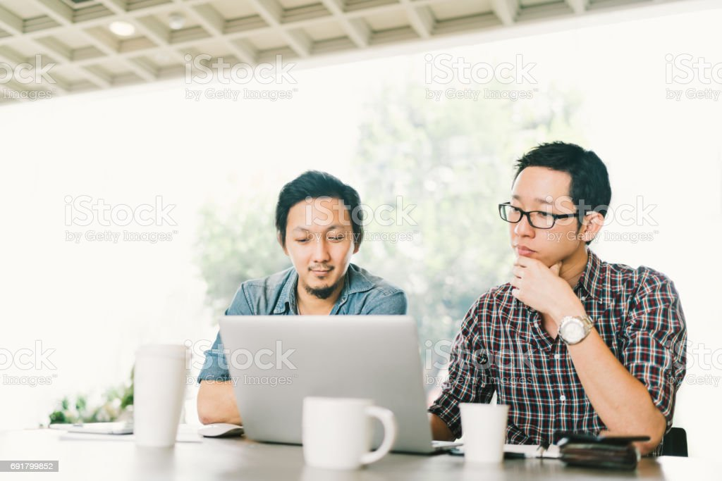 Handsome Asian business colleagues or college students work together using laptop, startup project meeting or teamwork brainstorm concept, at coffee shop or modern office stock photo