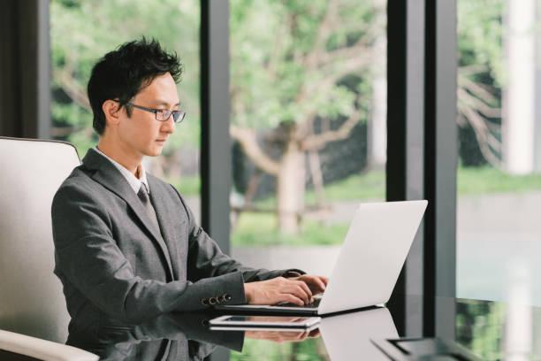 ハンサムなアジア系のビジネスマンやエグゼクティブ オフィスでラップトップ コンピューターとデジタル タブレットを使用して仕事、起業家。リーダーシップ、ビジネス コミュニケーション、スタートアップ、または情報の技術ガジェットのコンセプト - オフィスワーク ストックフォトと画像