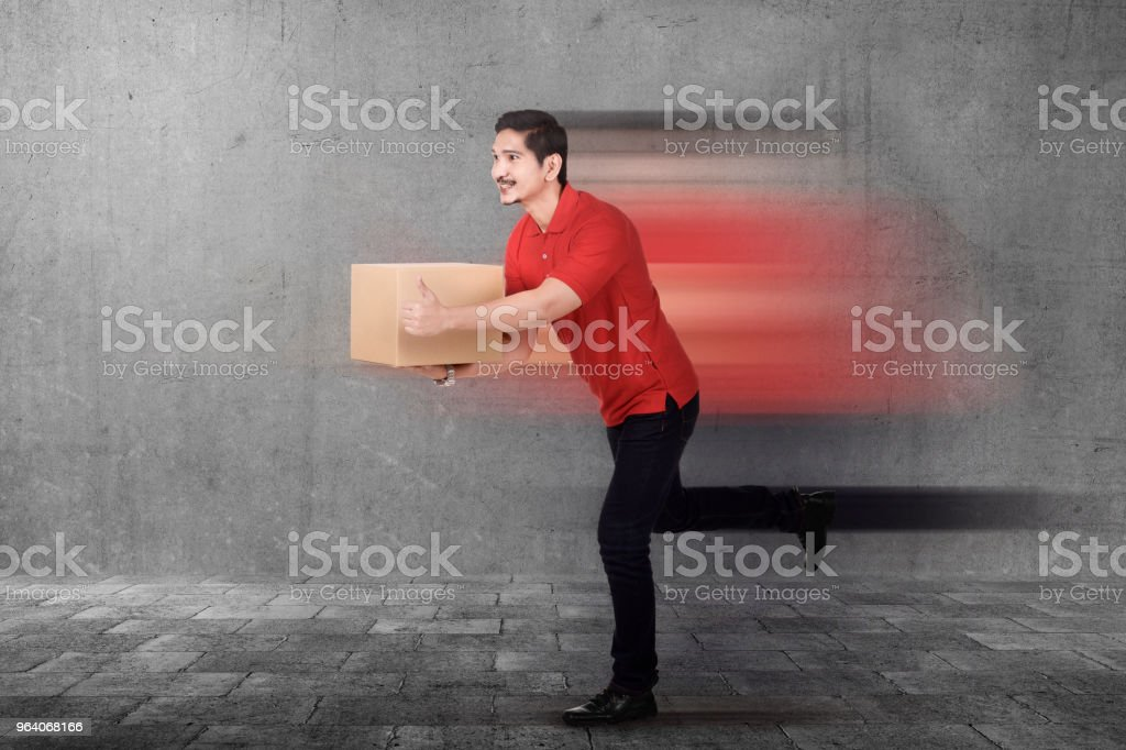 Handsome asian courier man delivering package - Royalty-free Adult Stock Photo