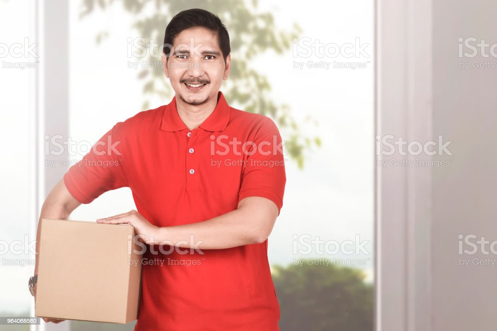 Handsome asian courier man holding the package - Royalty-free Adult Stock Photo