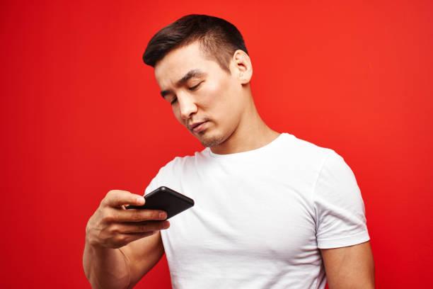 Handsome Asian Kerl im roten Studio schaut auf den Bildschirm des Mobiltelefons. Kasachischer Mann gekleidet lässig schreibt und liest SMS auf Smartphone – Foto