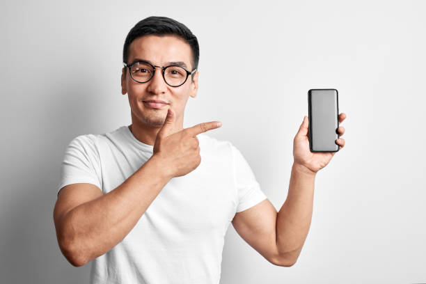 Handsome Asian guy in white studio smiles joyfully pointing index finger to screen of mobile phone. Happy man in glasses dressed casual holds and advertises smartphone