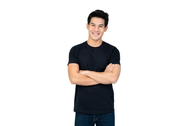 Handsome Asian man in casual black t-shirt with arm crossed Smiling handsome Asian man in casual black t-shirt with arm crossed looking at camera studio shot isolated on white background black shirt stock pictures, royalty-free photos & images