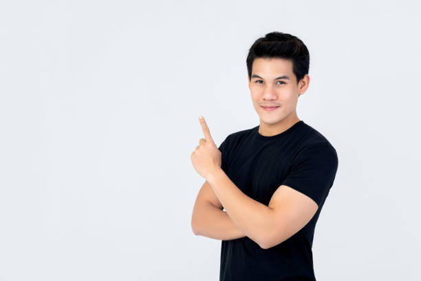 Handsome Asian man smiling and pointing hand upward to empty space stock photo