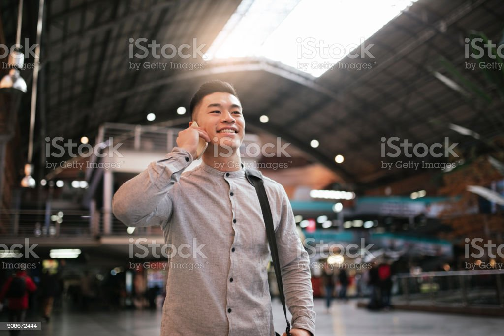 Handsome asian man using mobile in the train station. stock photo