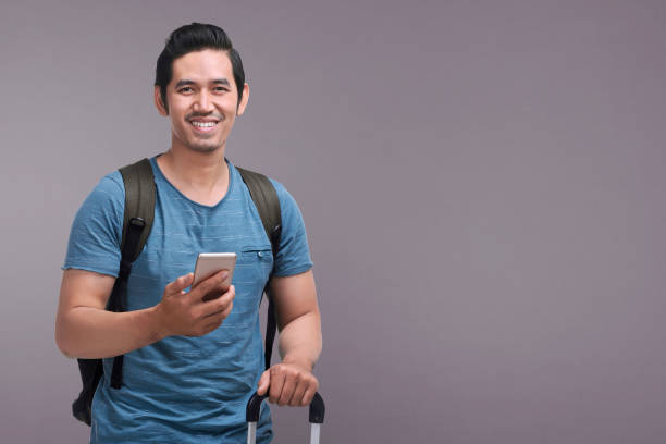 Handsome asian man using mobile phone while holding suitcase Handsome asian man using mobile phone while holding suitcase over dark color background indonesian ethnicity stock pictures, royalty-free photos & images