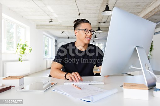 East asian computer programmer wearing black t-shirt sitting at the desk in the creative workplace. Young man typing.