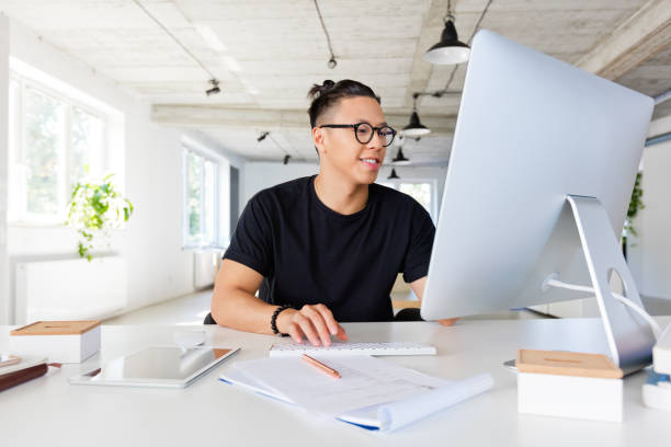 Handsome asian man working in the creative workplace stock photo