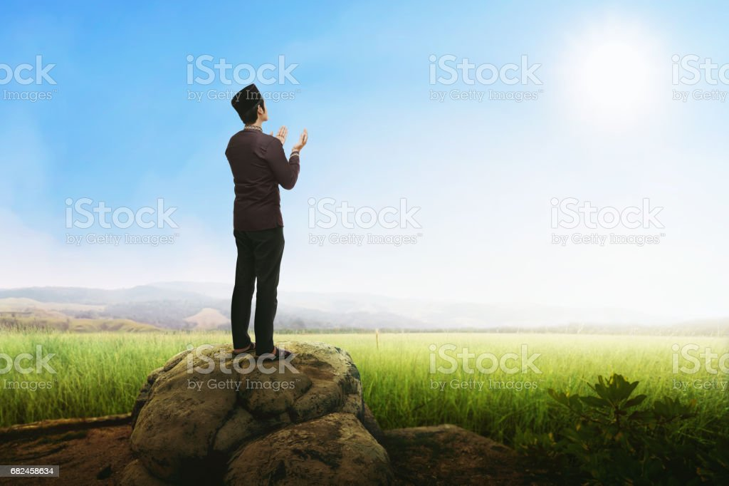 Handsome asian muslim man praying with standing on stone royalty-free stock photo