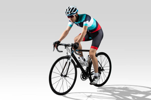 Handsome asian riders he is cycling .pretends to go downhill in the studio. stock photo