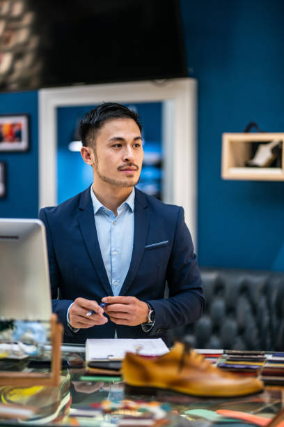 Handsome Asian shop assistant in shoe store stock photo