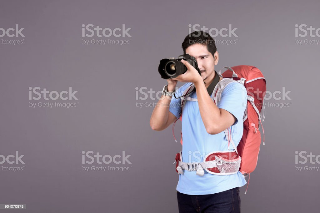 Handsome asian tourist with backpack using camera - Royalty-free Adult Stock Photo