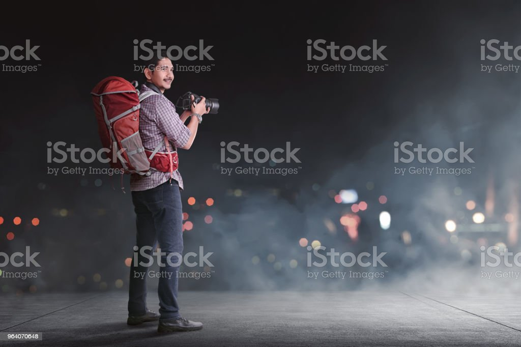 Handsome asian traveler with backpack and camera - Royalty-free Adult Stock Photo
