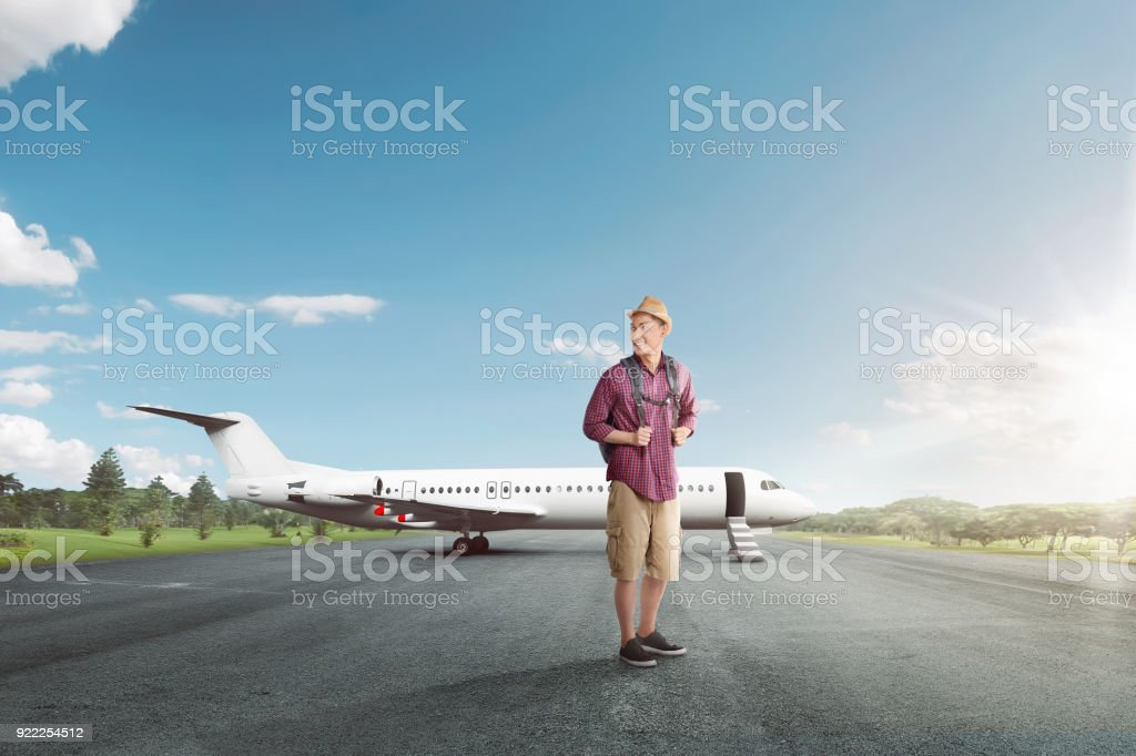 Handsome asian traveler with backpack ready to depart stock photo