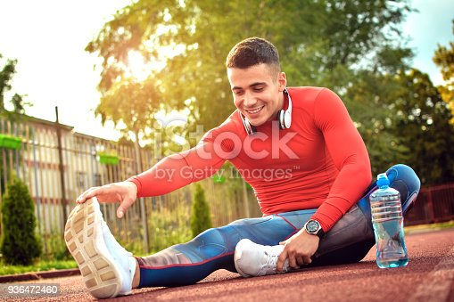 Handsome athlete is sitting on the road. He is stretching one leg forward while another leg is bent. He stretches himself with seriousness.