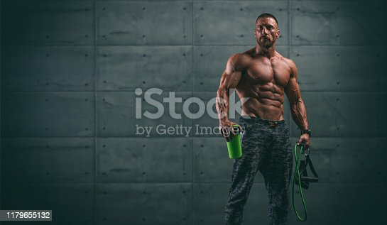 istock Handsome Athletic Men Holding Protein Drink Bottle and Resistance Bands 1179655132