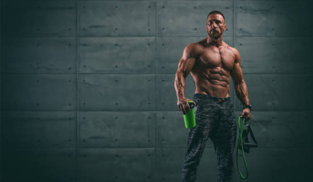 Handsome Athletic Men Holding Protein Drink Bottle and Resistance Bands stock photo