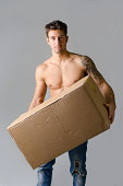 istock Handsome, athletic, shirtless young man carrying big cardboard box 450374675