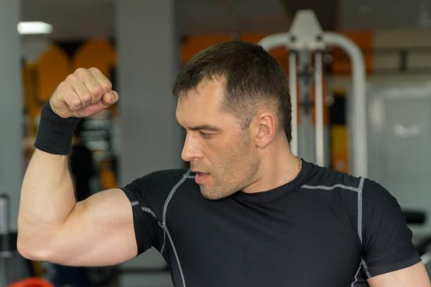 hübscher sportlicher junger Mann zeigt seine Bizeps posiert in Fitness-Studio – Foto