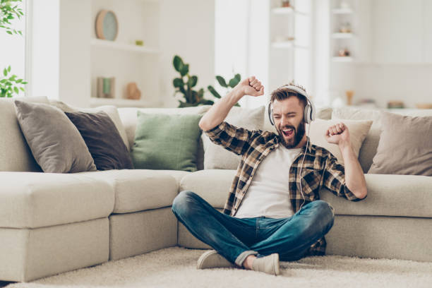 handsome attractive bearded young men wearing casual shirt and jeans, sitting at home on carpet, listening to music in headphones, raising hands up - gambe incrociate foto e immagini stock