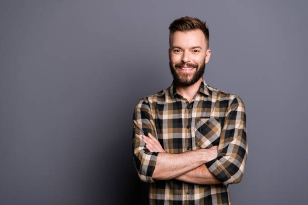 Handsome attractive bearded young smiling brunet men wearing casual, folded hands. Isolated over grey background Handsome attractive bearded young smiling brunet men wearing casual, folded hands. Isolated over grey background facial hair stock pictures, royalty-free photos & images