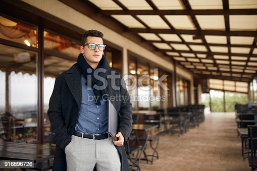 istock Handsome attractive businessman using a laptop on office terrace. Stylish man in glasses coat and scarf standing on balcony with laptop. Smart casual clothes. Business theme 916896726
