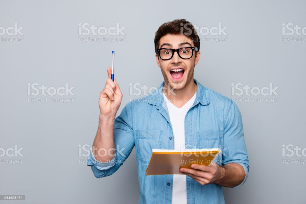 Handsome, attractive, glad, positive, funny guy in glasses with wide open mouth finally found a solution how to make exercise, having raised pen and notebook in hands, isolated on grey background stock photo