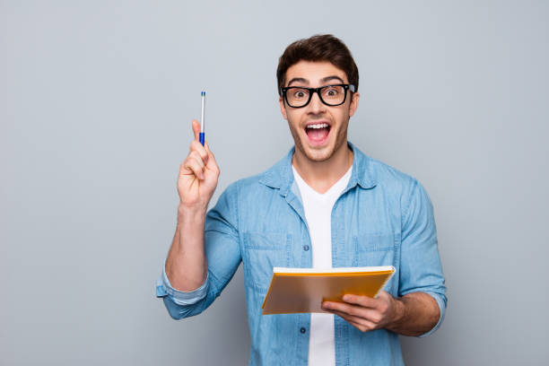Handsome, attractive, glad, positive, funny guy in glasses with wide open mouth finally found a solution how to make exercise, having raised pen and notebook in hands, isolated on grey background - foto stock