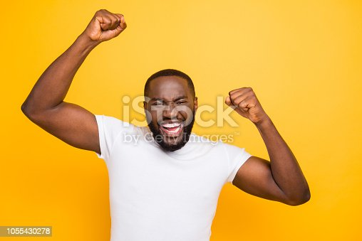1092211952 istock photo Handsome attractive manly cheerful glad mulatto man, showing winning yes cool gesture, celebrating, isolated over bright vivid yellow background 1055430278