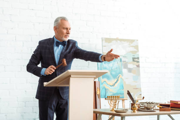 handsome auctioneer holding wooden gavel and pointing with hand during auction handsome auctioneer holding wooden gavel and pointing with hand during auction auction stock pictures, royalty-free photos & images