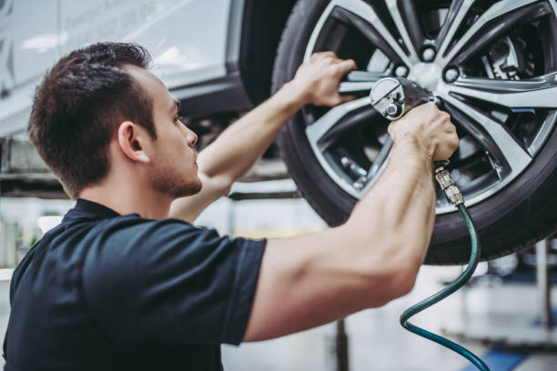 Handsome auto service mechanics. Handsome mechanic in uniform is working in auto service. Car repair and maintenance. Twisting/untwisting bolts on wheel. repairman stock pictures, royalty-free photos & images