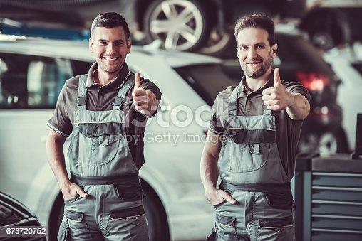 673723668 istock photo Handsome auto service workers 673720752