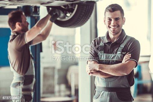 673723668 istock photo Handsome auto service workers 673723562