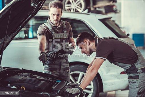 673723668 istock photo Handsome auto service workers 673729198