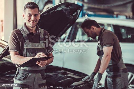 673723668 istock photo Handsome auto service workers 673729266