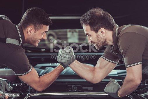 673723668 istock photo Handsome auto service workers 673729616