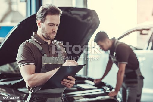 673723668 istock photo Handsome auto service workers 673730096