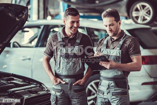 673723668 istock photo Handsome auto service workers 673732458