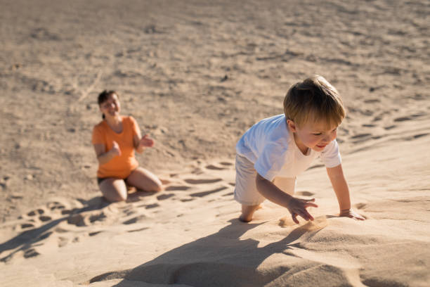 Handsome baby boy climbing on a sand dune with mother. stock photo