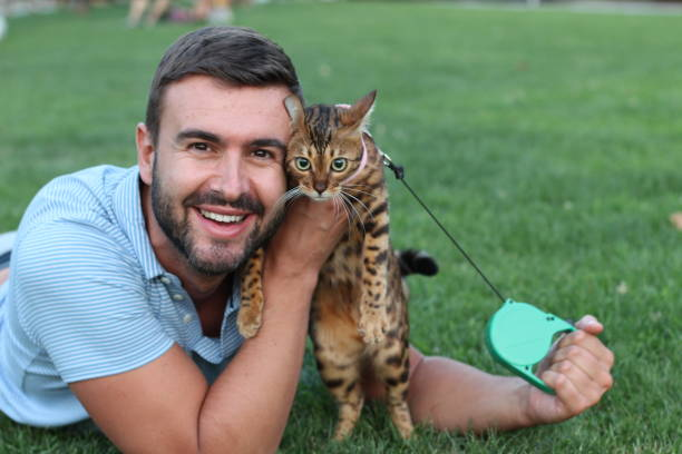 handsome bachelor with his pet outdoors - cat leash stock photos and pictures