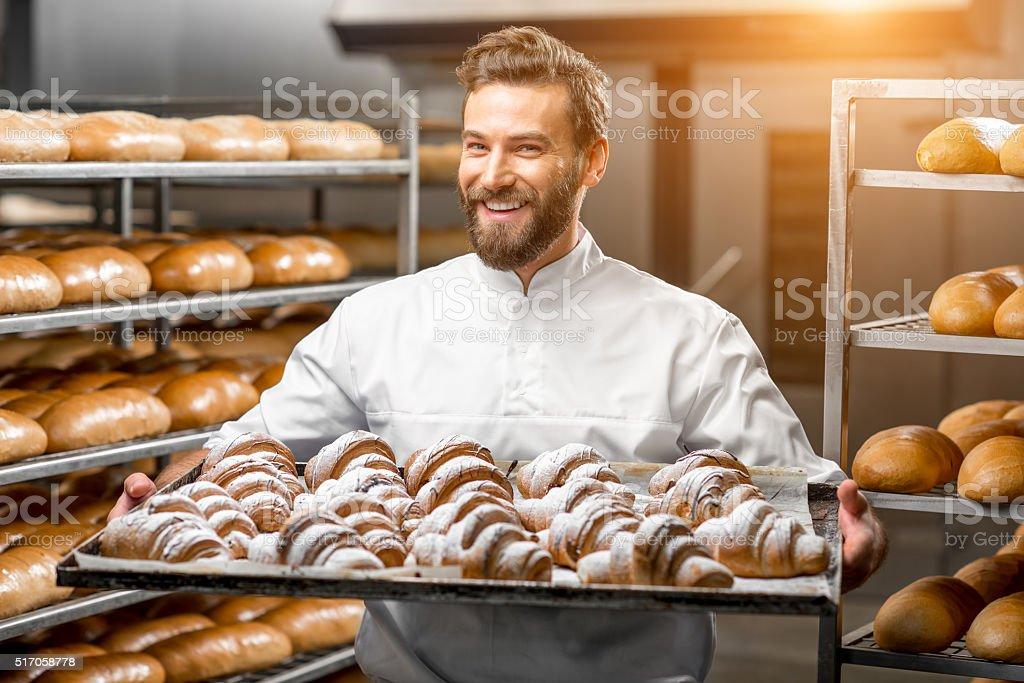 Handsome baker holding tray full of freshly baked croisants stock photo
