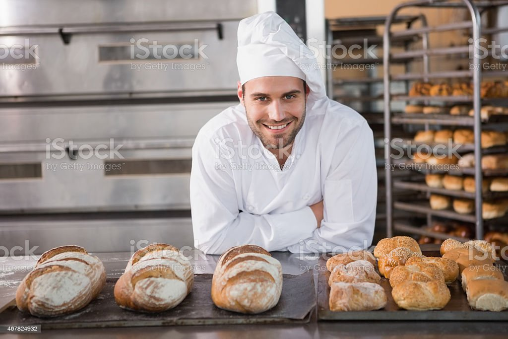 Handsome baker standing next to trays filled with bread stock photo