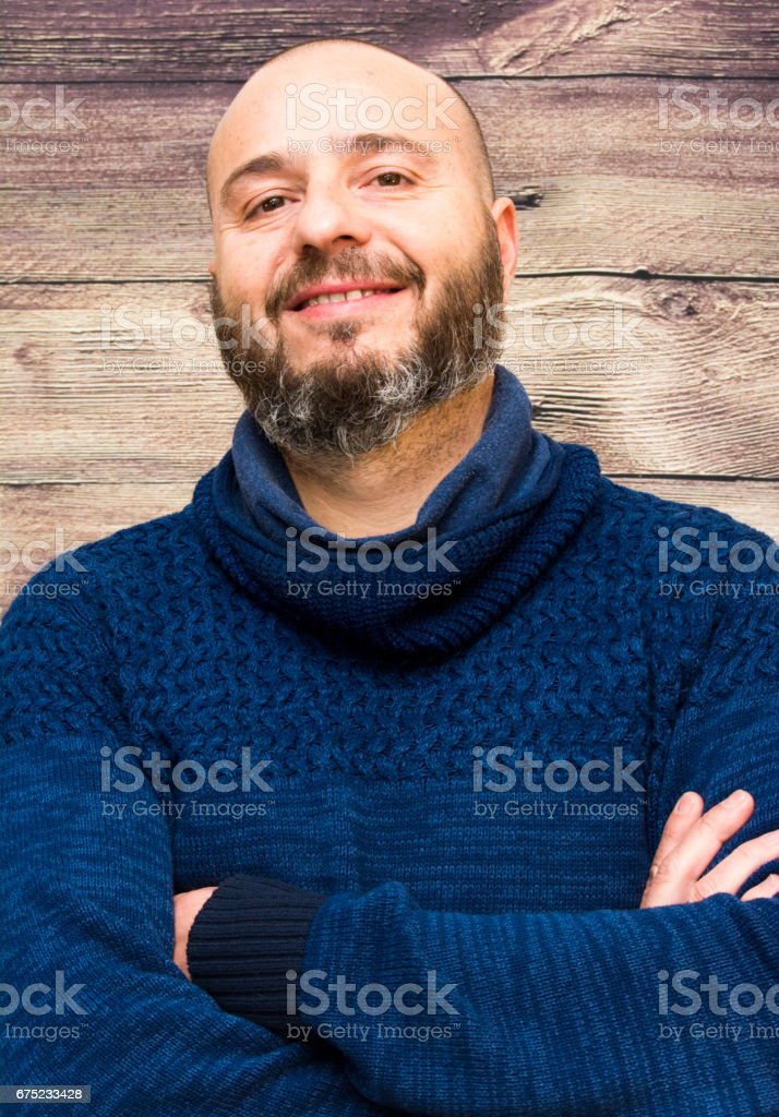 Handsome, bald man with beard  on a wooden background royalty-free stock photo