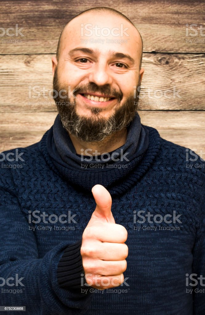 Handsome, bald man with beard  with her thumb up in sign of optimism  on a wooden background royalty-free stock photo
