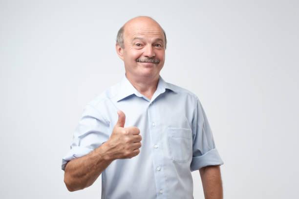 gut aussehend, glatzköpfiger mann mit seinem daumen im zeichen von optimismus auf weißem hintergrund - einzelner senior stock-fotos und bilder
