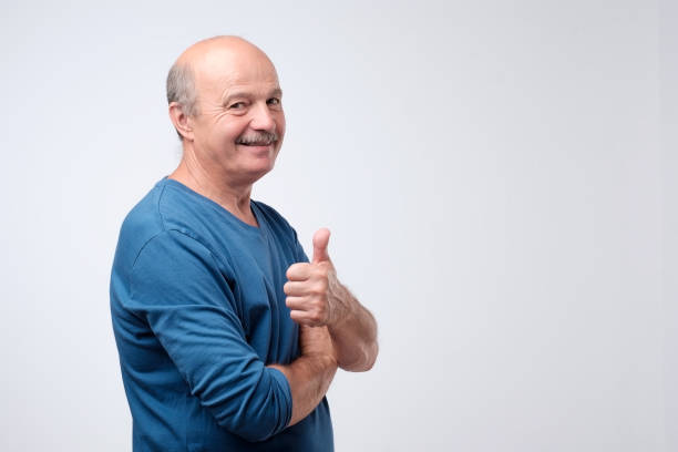 Handsome, bald man with his thumb up in sign of optimism on white background Handsome, bald man in blue t-shirt with his thumb up in sign of optimism on white background. Success in business or in personal life only senior men stock pictures, royalty-free photos & images