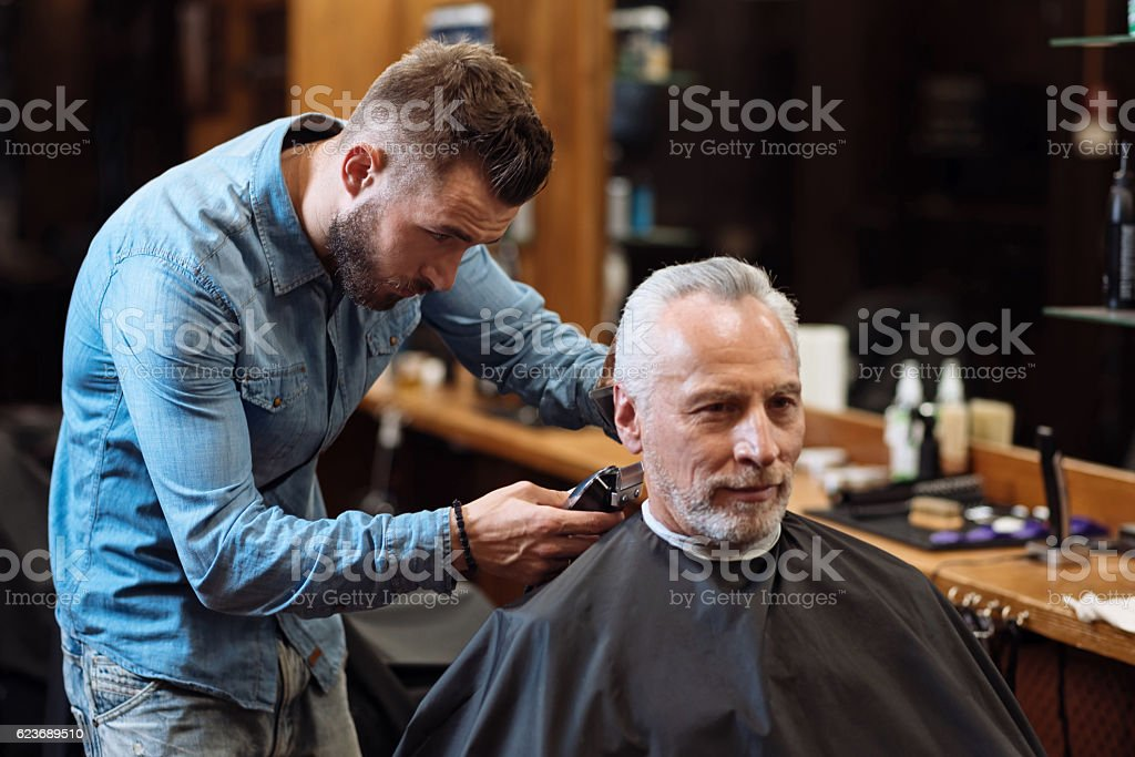 Handsome barber trimming hair of old man stock photo