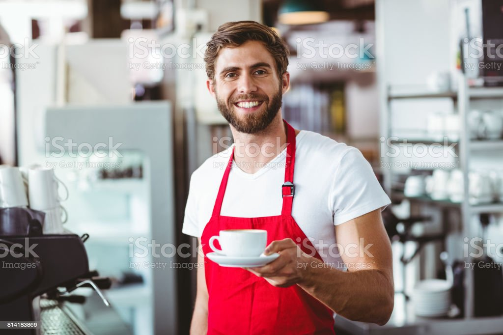 Handsome barista holding a cup of coffee stock photo