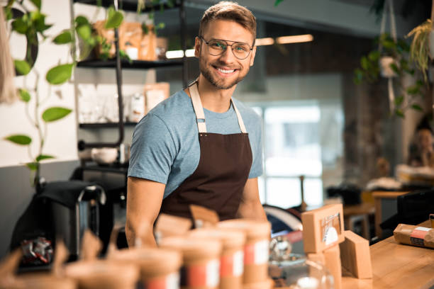 Handsome barista standing at the bar of modern cafe stock photo